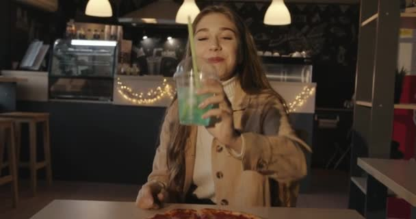 Attractive young blonde girl sits at a table in a cafe with pizza and holds out a glass with a blue cocktail with lemon and ice cubes to the camera