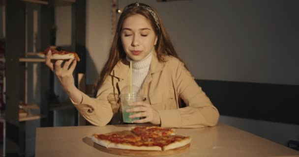 Cute young girl in a white sweater and beige jacket eats pizza in a cafe and drinks a blue cocktail with lemon through a straw