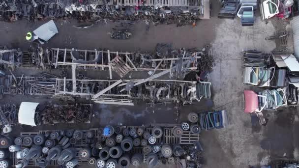 Dron střelba náhradních dílů pro automobily ležící na paletách ve venkovním skladu a mladý automechanik chůzi mezi řadami