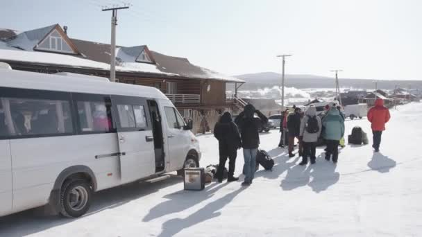 BAIKAL, IRKUTSK REGION, RUSSIA - MARCH 18, 2021: A group of tourists in winter stands near a minibus on a village street with wooden houses against a background of snowy mountains