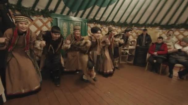 Irkutsk Region, Rusko - 18. března 2021: Buryatský folkový taneční soubor vystupuje před turisty ve velké jurtě jako součást exkurze podél pobřeží jezera Bajkal