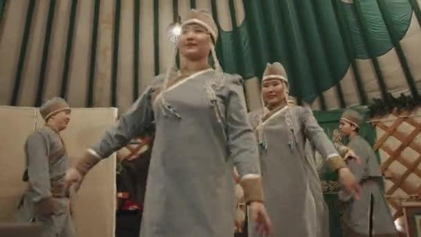 Irkutsk Region, Rusko - 18. března 2021: Buryatští tanečníci v národních kostýmech vystupují na koncertě v jurtě pro turisty v rámci exkurze do etnoparku