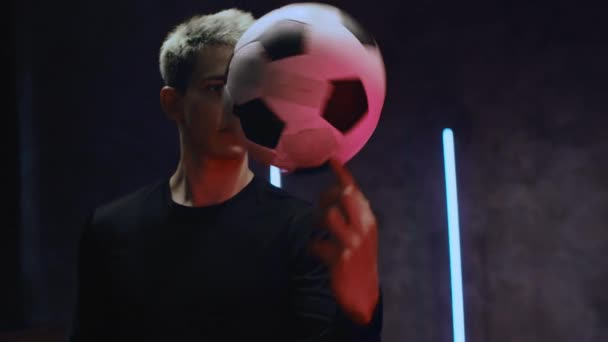 A handsome young soccer player in a black jersey stands in a dark studio in the light of neon lights and twirls a soccer ball on his finger. 4K