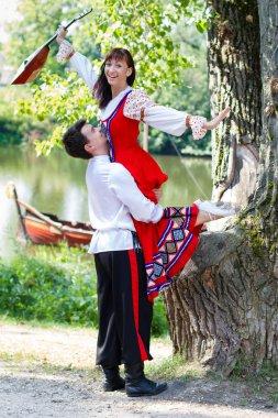 Couple in dress suit stylized Ukrainian folk dancing