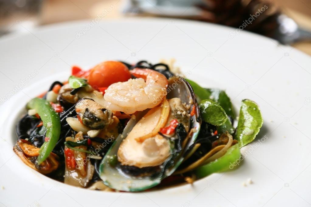 Spaghetti mit Garnelen und Meeresfrüchte auf weißen Teller, schwarze ...