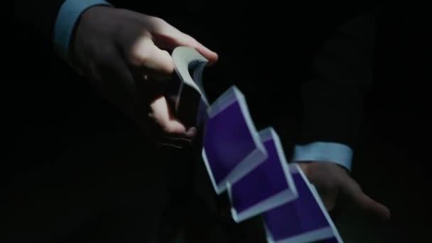 Video von männlichen Händen, die bei schwachem Licht professionell Karten mischen