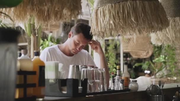 mladý muž čte menu ve venkovním baru u baru