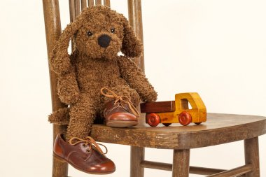 Cute Soft toy puppy sitting on a chair in old leather shoes