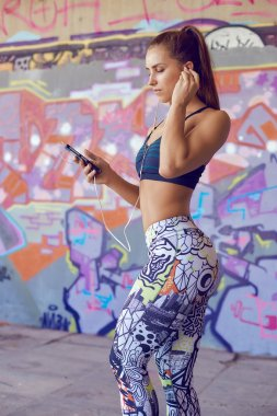 Young fitness woman in sportswear listening music with headphones