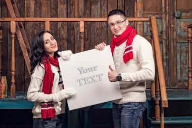 Couple in winter clothes hold blank board