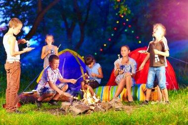 happy kids around bonfire in summer camp