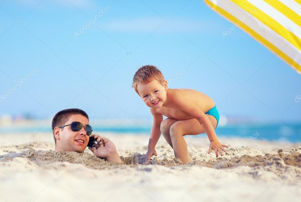 kid playing around father's head in sand, talking on the cell phone