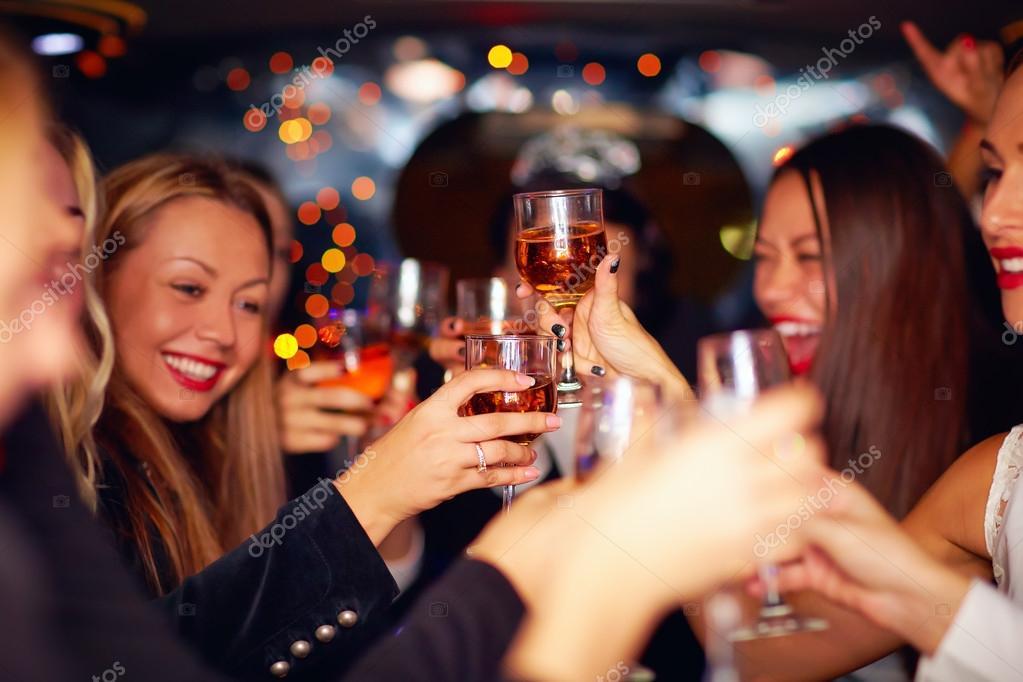 beautiful women clinking glasses in limousine