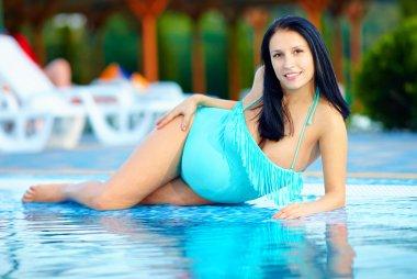 beautiful pregnant woman posing near the pool