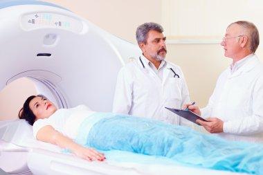 two doctors preparing patient to CT scanner procedure