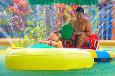 Family drive watercraft in aqua park, trying to hit each other