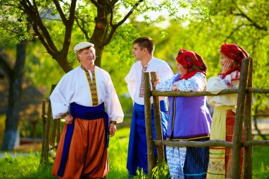 happy ukrainian family in traditional costumes talking near the country house