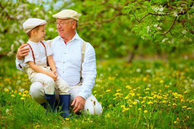 happy grandfather and grandson in spring garden