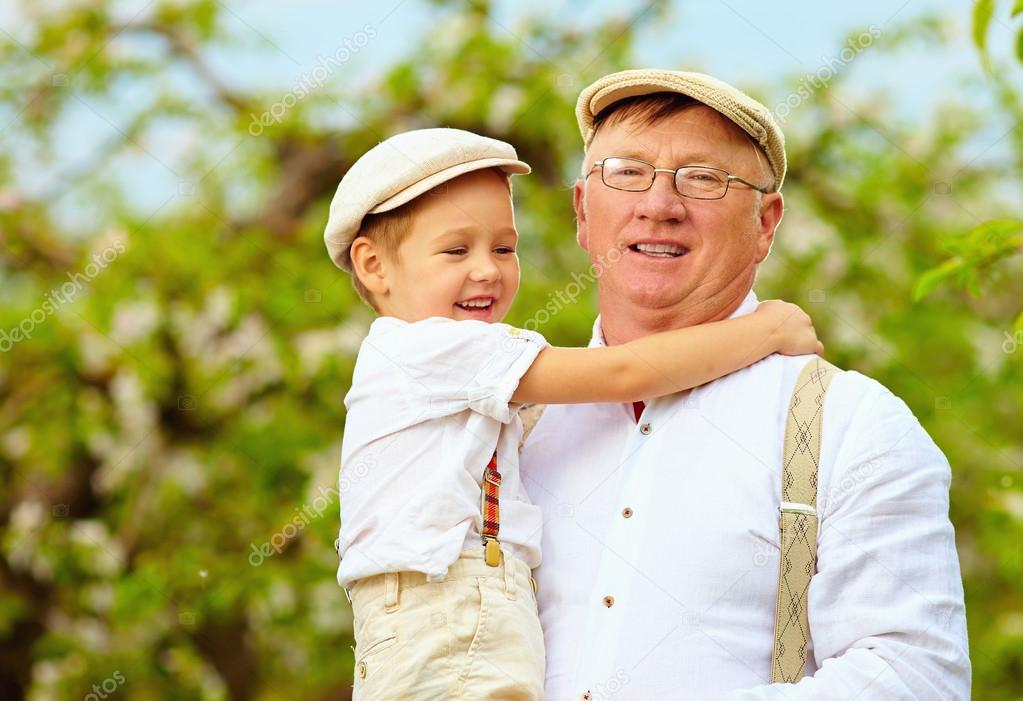 cute grandpa with grandson on hands in spring garden