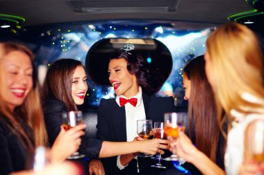 group of happy elegant women clinking glasses in limousine, hen party