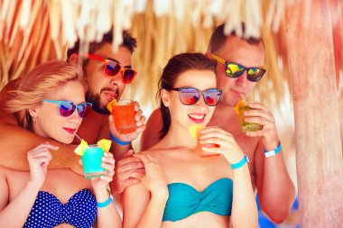 group of happy friends having fun on tropical beach, drinking colorful cocktails