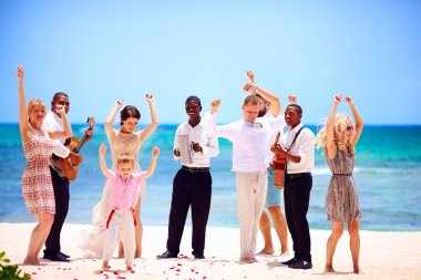 group of happy family on celebration the exotic wedding with musicians, on tropical beach