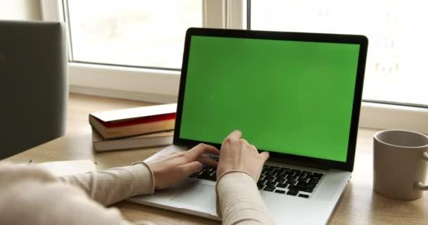 Egy üzletasszony válla fölött, aki irodai belsőben dolgozik az íróasztalon, és a zöld képernyőt nézi. Irodai személy laptop számítógép laptop zöld képernyő, ül a fa asztal