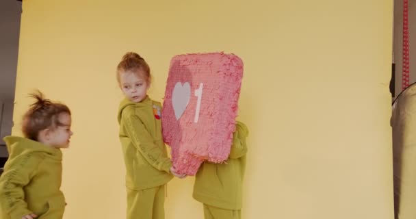 Drei lustige Kinder in Freizeitkleidung posieren mit ähnlicher Ikone im Studio. Gelber Hintergrund. Soziales Netzwerk und Feedback-Konzept.