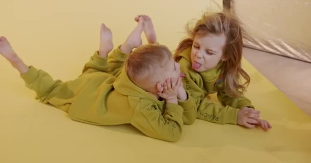 Group of two happy kids lying together on floor and showing tongues to each other. Joyful children in casual jumpsuits playing in studio with violet background.