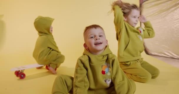 Skupina tří šťastných dětí oblečených v podobných kombinézách, které si spolu hrají na žlutém pozadí. Radostné děti tráví čas se zábavou ve studiu.