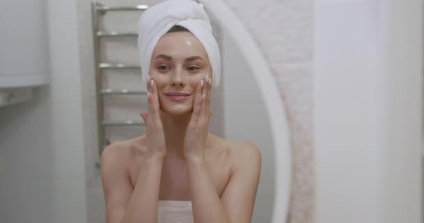 Krásná mladá žena s ručníkem na hlavě nanášení hydratační krém na obličej po sprše. Hezká dáma dělá hydratační procedury pro pleť doma.