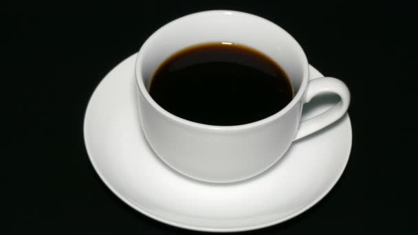 White cup black coffee on black background