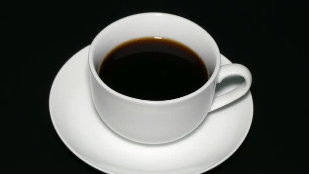 Bílý šálek černé kávy na černém pozadí