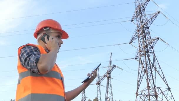 Inženýr pracující. Telefonovat a pracuje na tabletu. Kontrola energetických sítí.