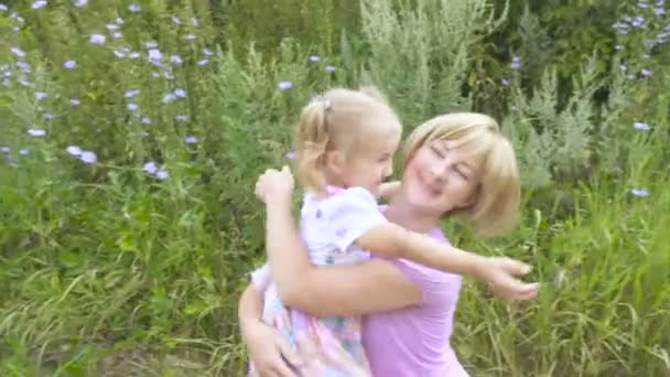 Mother and child are hugging and having fun outdoor in park, mother hugs and kissing her little cute daughter