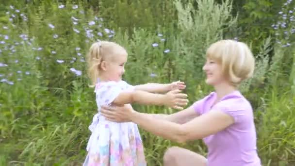 Matka a dítě jsou objímání a baví venkovní v parku, matka objetí a polibky její malá roztomilá dcera