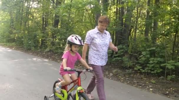 Großmutter lernt Fahrradfahren kleine Enkelin. glückliches Kind beim Fahrradfahren im Park im Freien. Zeitlupe.