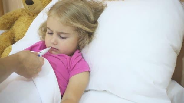 Nemocná malá holčička s její teploty s digitálním teploměrem. Dítě s horečkou: žena je měření teploty dítěte. Detail