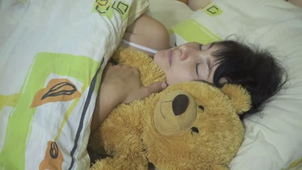 Mladá žena, dívka spící v posteli objímající medvídka .