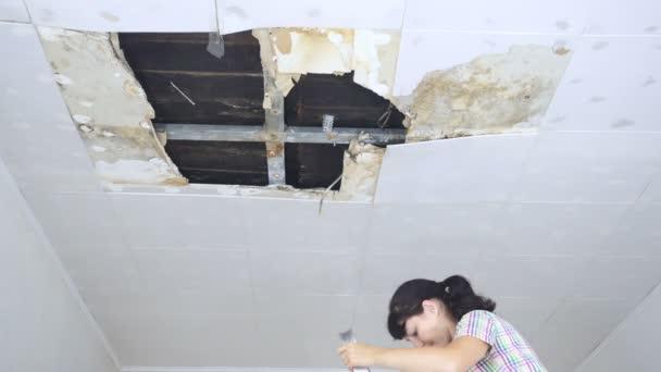 Jonge vrouw verzamelen van Water In bekken van plafond ...