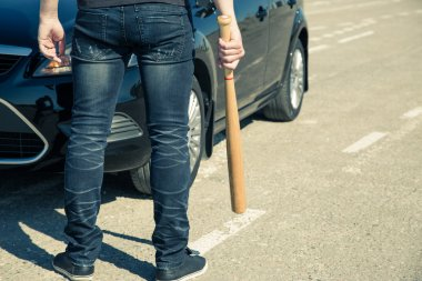 Man with baseball bat on the road before the car