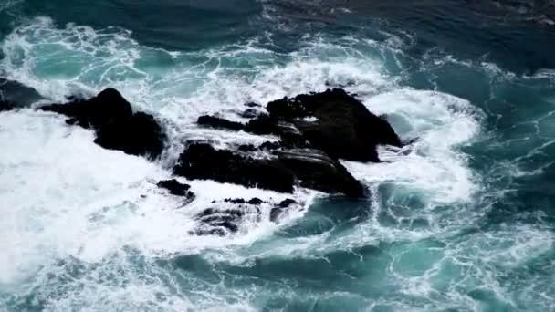 Vlny praskajících na černých skalách
