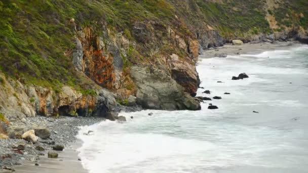 Hullámok fut a sziklás tengerpart