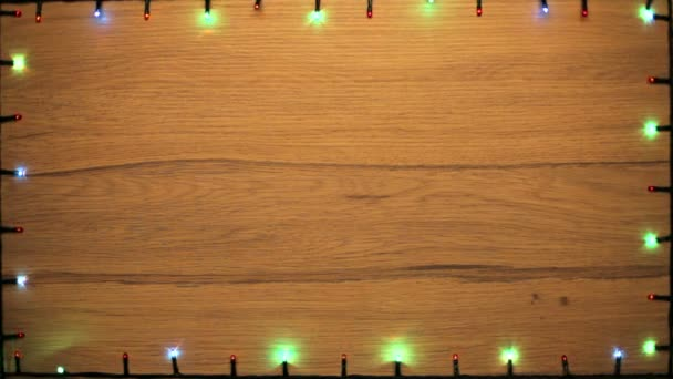 Flickering Christmas lights of different colors frame on a wooden board