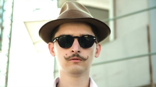 man with a mustache wearing sunglasses and a hat