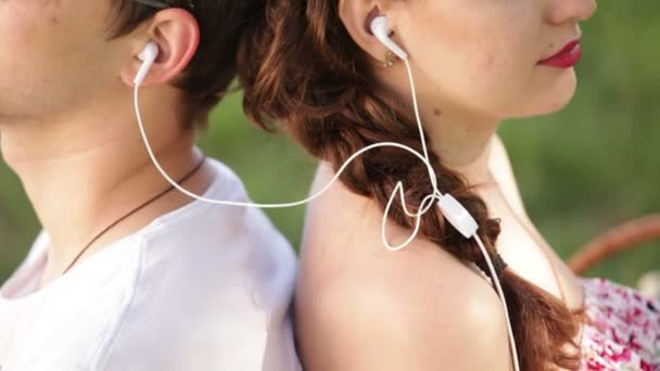 man and woman sitting back to back in the park and listen to music
