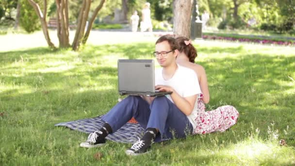 man and woman sitting back to back in the park and working with a laptop
