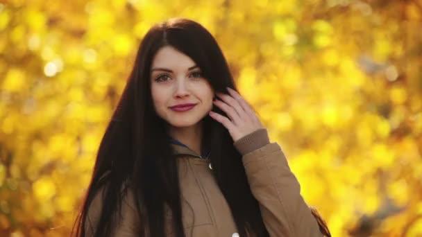 mladá dívka posingon pozadí žluté listy