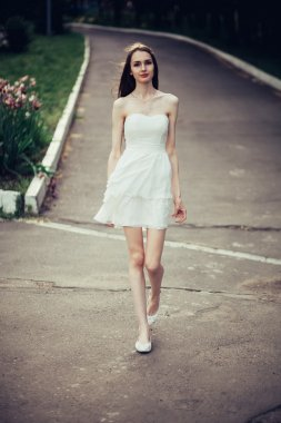 Young woman in white dress goes