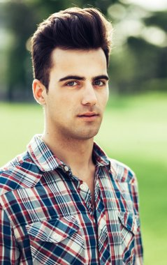portrait of a young man in plaid shirt